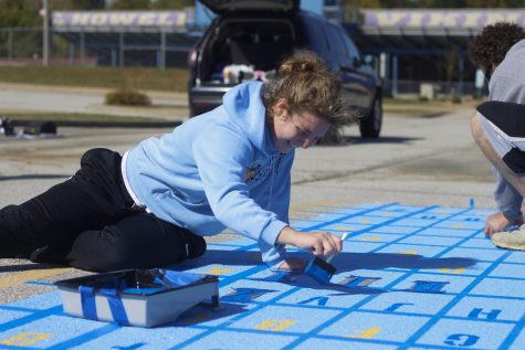 Senior Lilli Machado paints her parking spot.