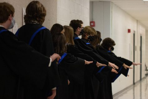 Concert Choir puts their hands in the middle with choir director Karey Fitzpatrick to cheer for their concert performance on Nov. 17.