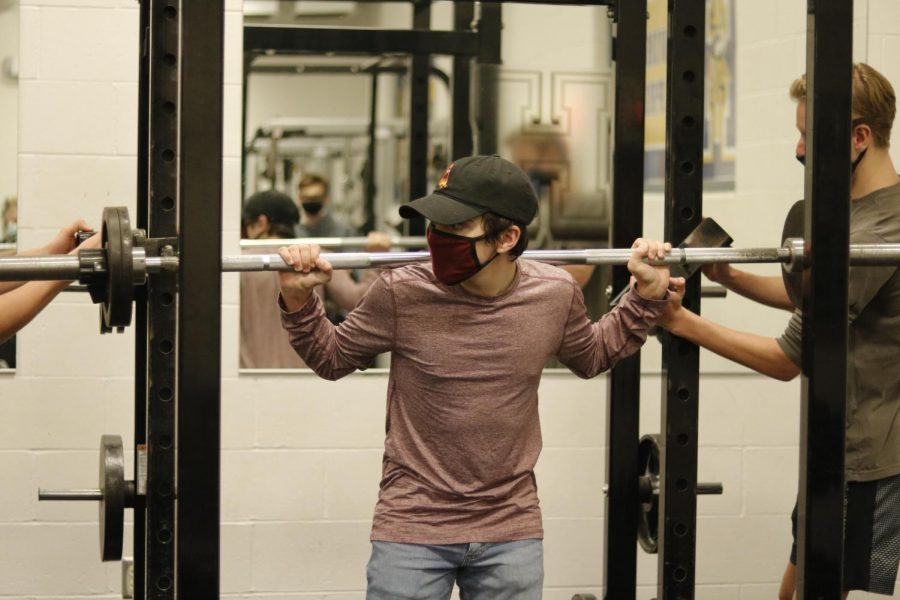 "Nov. 24, junior Aidan Ferrar squats 85 pounds with the assist of his classmates Nov. 23. ""Weight training has left me feeling more and more confident lately and I"